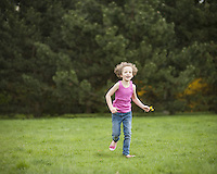 Young girl running through park in summer