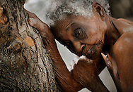A resident leans against a tree for support as she waits to bathe at the Azil Communal home for the aging population in Port-Au-Prince, Haiti, on Monday, March 8, 2010. (photo by Nikki Kahn/ The Washington Post)