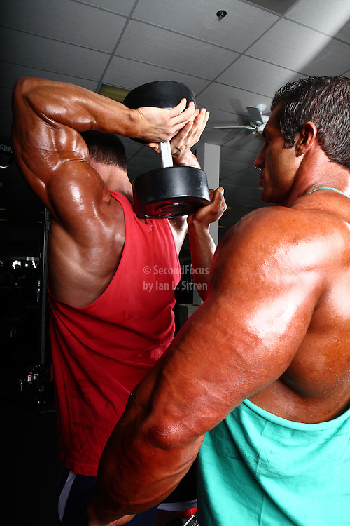 Bodybuilders Dan Decker and Brian Yersky overhead triceps workout with a dumbbell.