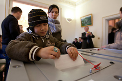 © licensed to London News Pictures. London, UK 04/03/2012. A boy placing his mother's vote to a ballot box at The Embassy of the Russian Federation in London as the elections for the President of the Russian Federation take place today (04/03/12). Photo credit: Tolga Akmen/LNP