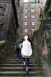 Musician carrying cello up narrow lane during Edinburgh Festival 2016 in Scotland, United Kingdom