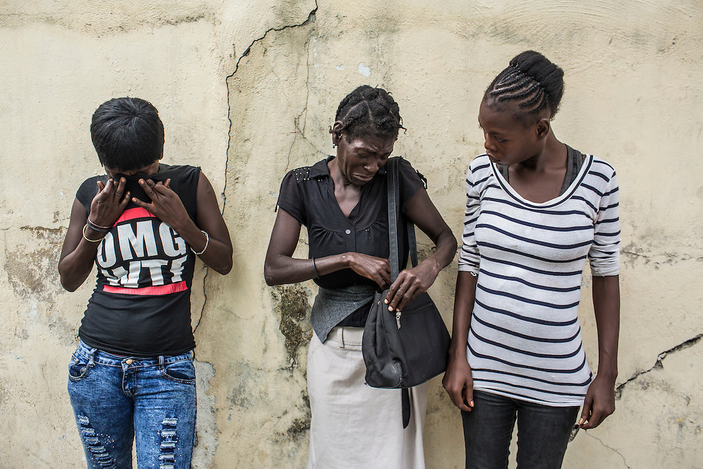 Betty Nicolas, Claudiani Fonrose, and Bertha Nicolas, from left, cry after posing for a picture on Monday, December 15, 2014 in Port-au-Prince, Haiti. They are the sisters and mother of Jolin Nicolas, 19, who was killed while participating in an anti-government protest on December 13.