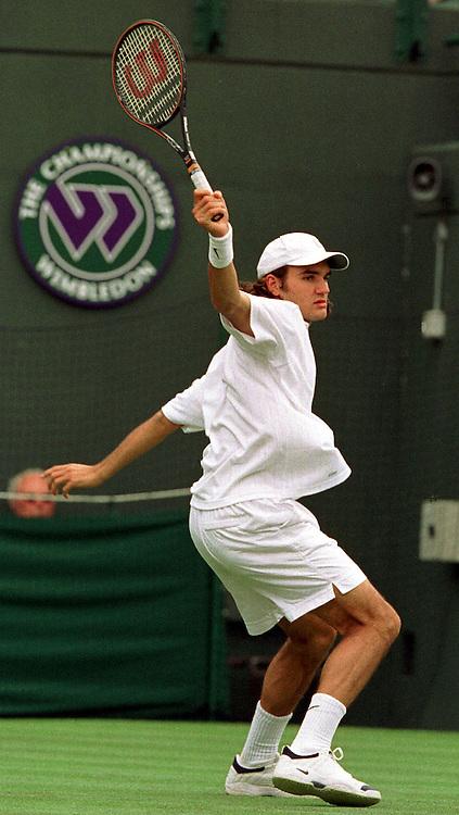 Sport,Tennis,Wimbledon 2000,Grand Slam Turnier,Spieler Roger Federer (SUI) in Aktion,action, Rueckhand Return,Schlagende,Schlaeger,Racket oben, weisse Kappe, Hochformat,ganze Figur, Hintergrund Wimbledon Logo,