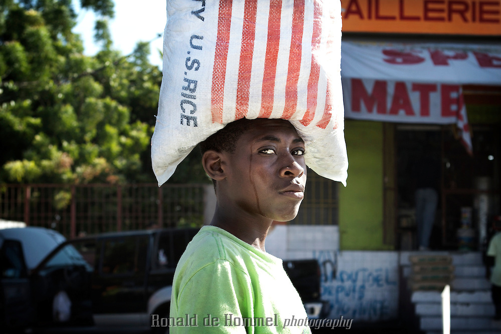 A boy sell water in the streets of Port au Prince. On his head a bag of American rice..Cheap rice imports from the USA, have virtually destroyed the agricultural sector in Haiti in the nineties. The aftermath of the earth quake of January 12, 2010 might be a good moment to take up the restructuring of the agricultural sector in the country to make it more self sustainable for the future.
