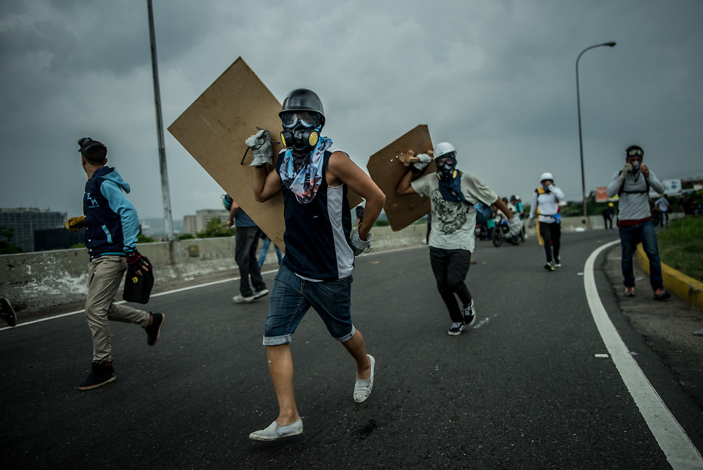 CARACAS, VENEZUELA - MAY 10, 2017:  Anti-government protesters with homemade shields run as National Guard soldiers on motorcycles shooting rubber bullets and buckshot chase them during clashes to take control of Francisco Fajardo highway.  The streets of Caracas and other cities across Venezuela have been filled with tens of thousands of demonstrators for nearly 100 days of massive protests, held since April 1st. Protesters are enraged at the government for becoming an increasingly repressive, authoritarian regime that has delayed elections, used armed government loyalist to threaten dissidents, called for the Constitution to be re-written to favor them, jailed and tortured protesters and members of the political opposition, and whose corruption and failed economic policy has caused the current economic crisis that has led to widespread food and medicine shortages across the country.  Independent local media report nearly 100 people have been killed during protests and protest-related riots and looting.  The government currently only officially reports 75 deaths.  Over 2,000 people have been injured, and over 3,000 protesters have been detained by authorities.  PHOTO: Meridith Kohut