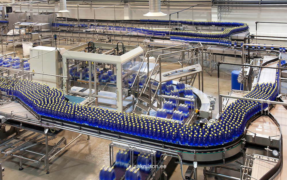 Production process inside a drinks manufacturer, and processing plant. Mineral water bottles being passed along on a moving conveyor belt, for labelling and shrinkwrapping. Yellow tops. Four and six bottle packs wrapped.