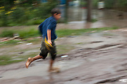 A boy steps on a puddle as he runs under the rain through the streets of Ocho de Mayo.