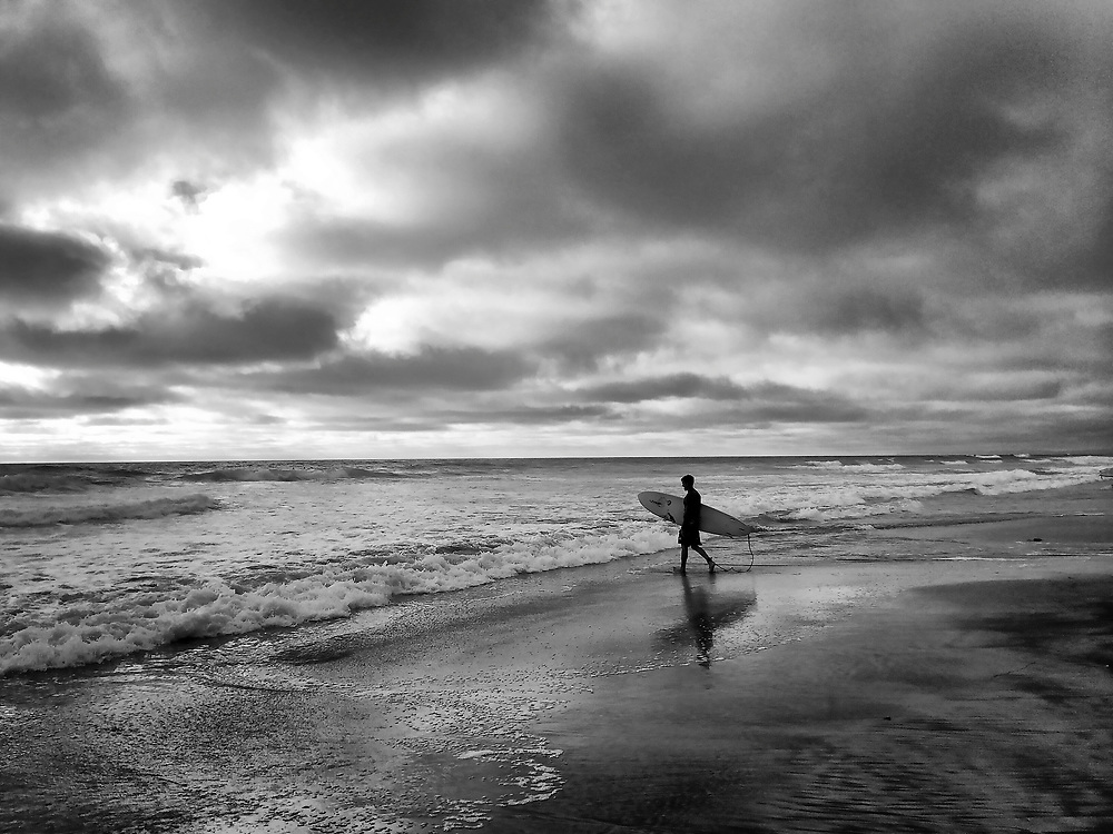 Surfer heading out at sunset at Del Mar Beach in Del Mar, CA.