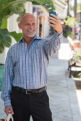 man enjoying taking a selfie while standing on Las Olas Blvd in Fort Lauderdale, Florida