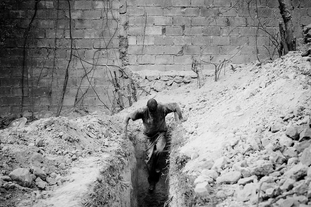 A man climbs down into a pit he is digging to build latrines in a camp for those displaced by the recent earthquake in Petionville, outside Port-au-Prince, Haiti.