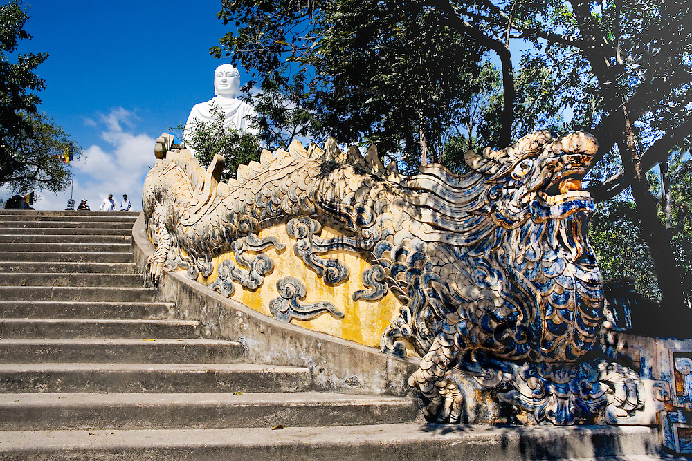 """View looking up the dragon (Vietnamese: rá""""ng or long) staircase approach to Buddha statue on the hill at Hai Duc Pagoda, above Long Son Pagoda. The Vietnamese dragon is the symbol of yang, representing the universe, life, existence, and growth.  Its head in the right foreground, its body snakes up the stairs as a balustrade, while the white Buddha soars above."""