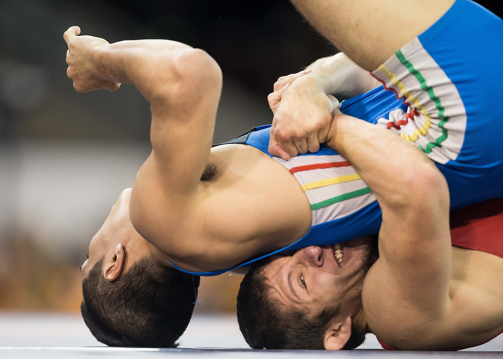 Cristsbal Torres of Chile (R) throws Marvin Chavez of Bolivia in their quarter final bout in the 59kg class of the men's greco-roman wrestling  at the 2015 Pan American Games in Toronto, Canada, July 15,  2015.  AFP PHOTO/GEOFF ROBINS