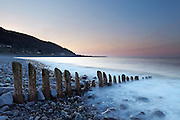 Waves washing over rocks, split by a groyne, at dusk, with the village of Porlock Weir in the background.