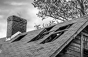 Decay has taken a toll on the roof of this abandoned house. The repetitive texture of roofing shingles is interrupted by large gaping holes in the supporting roof structure.