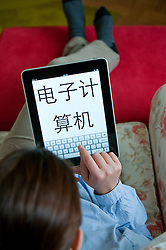 Woman using iPad tablet computer at home to study Chinese language using self study education application