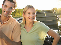 Portrait of couple outdoors standing by jeep smiling