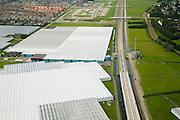 Nederland, Zuid-Holland, Bleiswijk, 08-09-2006;  ; HSL loopt langs het kassengebied van Bleiswijk, gedeeltelijk in een verlaagde bak;   links aan de horizon de VINEX nieuwbouwwijk van Bergschenhoek; de dijk rechtsboven is de Landscheiding van Delfland en Schieland, vroegere grens tussen de waterschappen / hoogheemraden; waterbeheer, glastuinbouw, biocultuur, kweken, tuinbouw, landbouw, transport, infrastructuur, verkeer en vervoer, mobiliteit, hogesnelheidslijn, spoor, rail, HSL, TGV, planologie, ruimtelijke ordening, landschap; .zie ook detailfoto en panorama foto van deze lokatie; deel van de serie Panorama Nederland luchtfoto (toeslag); aerial photo (additional fee required); .foto Siebe Swart / photo Siebe Swart
