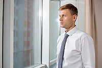Thoughtful mid adult businessman looking through window at home