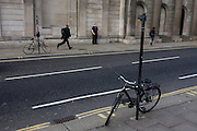 Londoners and two bicycles locked to posts on opposite sides of the road outside the Bank of England in the City of London.