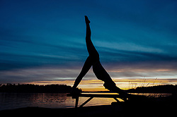 February 9, 2016 - Woman practising yoga by lake at sunset (Credit Image: © Image Source via ZUMA Press)