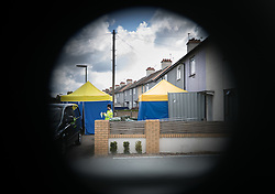 © Licensed to London News Pictures. 18/09/2017. London, UK. In this image taken through a barrier a policeman stands outside the house (R) in Sunbury, west London, where detectives investigating the Parsons Green tube bombing are continuing to search for clues. Investigations are continuing into the failed bombing of an underground train at Parsons Green station on September 15, 2017. Detectives have searched three properties and have two people in custody. Photo credit: Peter Macdiarmid/LNP