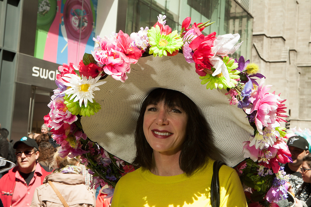 A woman in a large hat adorned with several varieties of fresh flowers.