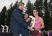 Dec 1, 2018; Portland, OR, USA; Nike chief executive officer Mark Parker(left) presents Liam Anderson with the winner's trophy during the Nike Cross Nationals at Glendoveer Golf Course.
