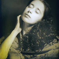 A monochromatic portrait of a woman with curly hair, with eyes closed and a dreamy expression.