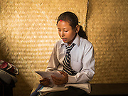 02 AUGUST 2015 - BHAKTAPUR, NEPAL:  A student at Sharada Higher Secondary School in Bhaktapur studies in a temporary classroom made out of woven mats before an exam. About half of the school was destroyed in the earthquake that struck in April 2015. The school is being rebuilt by the staff in their spare time. The Nepal Earthquake on April 25, 2015, (also known as the Gorkha earthquake) killed more than 9,000 people and injured more than 23,000. It had a magnitude of 7.8. The epicenter was east of the district of Lamjung, and its hypocenter was at a depth of approximately 15km (9.3mi). It was the worst natural disaster to strike Nepal since the 1934 Nepal–Bihar earthquake. The earthquake triggered an avalanche on Mount Everest, killing at least 19. The earthquake also set off an avalanche in the Langtang valley, where 250 people were reported missing. Hundreds of thousands of people were made homeless with entire villages flattened across many districts of the country. Centuries-old buildings were destroyed at UNESCO World Heritage sites in the Kathmandu Valley, including some at the Kathmandu Durbar Square, the Patan Durbar Squar, the Bhaktapur Durbar Square, the Changu Narayan Temple and the Swayambhunath Stupa. Geophysicists and other experts had warned for decades that Nepal was vulnerable to a deadly earthquake, particularly because of its geology, urbanization, and architecture.      PHOTO BY JACK KURTZ