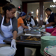 Kitchen volunteers preparing and serving food for the homeless.<br />