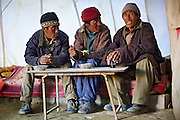 Three Himalayan villagers talking and having an evening snack together in a local restaurant of Korzok Village near Tso Moriri lake, Ladakh