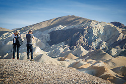 Photographers above eroded badlands and ravines, Twenty Mule Team Canyon, Death Valley National Park, California, USA