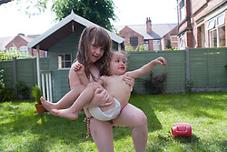Little girl picking up her younger sister in the garden,