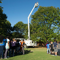 Communication assistant Ryan Coon waits in the Tupelo Water and Light bucket truck for students and staff to get organized to spell out 'PSE 50th' before taking a photo Friday morning at Pierce Street Elementary School. The photo was taken to commemorate the 50th anniversary of the school.
