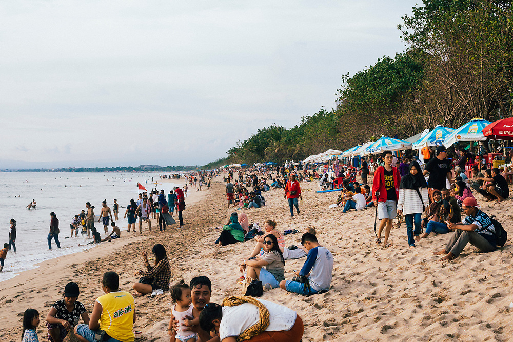 Crowds gather to take in the late afternoon sun near Legian beach in Kuta in Bali. Indonesia.