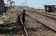 Children play along trian tracks in the village of Egodauyana near Moratuwa, Sri Lanka March 13, 2005. Several families in the village were paid 2500 Sri Lankan Rupees(US $25) to leave government refugee camps and return to their homes which are less than 50 meters from the Indian Ocean only to have the Sri Lankan government respond to the December 26, 2004 tsunami by putting forth a proposal restricting the builing of structures within 100 meters of the shore.