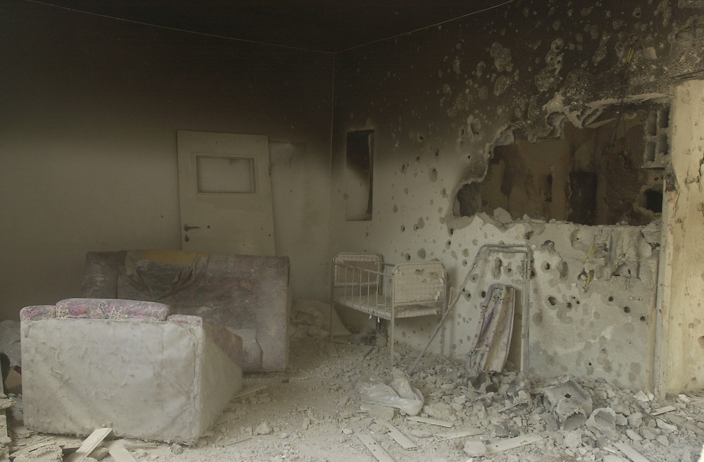 A baby's cot sits in a bullet ridden living room in the West Bank refugee camp of Jenin, Sunday April 21, 2002. The Jenin camp was the scene of a week of intense fighting between Israeli troops and Palestinian gunmen. The Palestinians say hundreds died, including civilians, when Israeli forces demolished more than 100 homes.