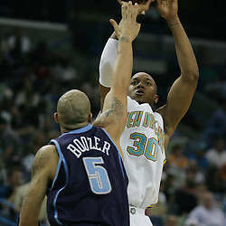 New Orleans Hornets forward David West #30 shoots over Carlos Boozer #5 of the Utah Jazz in the first quarter of their NBA game on April 8, 2008 at the New Orleans Arena in New Orleans, Louisiana.