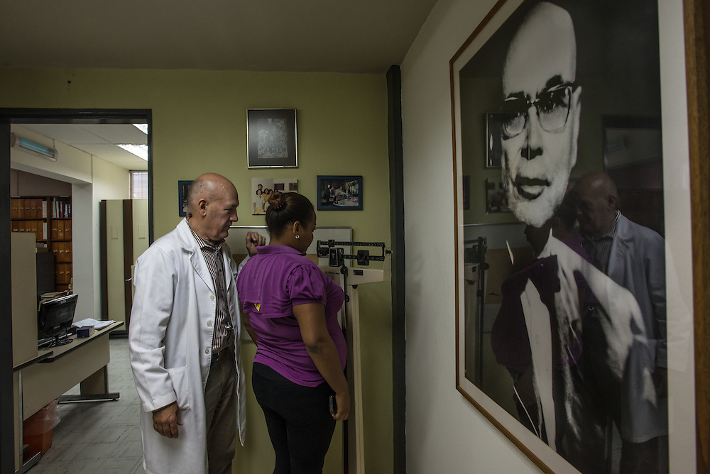 "CARACAS, VENEZUELA - JUNE 1, 2016:  Dr. Oscar Noya, an infectious disease expert, conducts a check-up with Gleidys Nieves, who is 7-months pregnant and sick with Plasmodim falciparum, the most fatal and severe form of malaria. She lives in Las Claritas with her husband, who is an illegal gold miner. She said he earns an average of one million bolivares a month working in the mines, the money is so good, (approximately 30 times more than a monthly minimum wage for full-time workers in large cities) that they will not leave the mine, despite the malaria. This is the 10th time Mrs. Nieves has contracted malaria.  She decided to travel to Caracas to be treated and monitored by Dr. Noya, because of her pregnancy.  Because few imports now arrive to the country Dr. Noya lacks many drugs he needs, like artesunate, listed by the WHO as an ""essential medicine"" for the treatment of severe cases of malaria. Dr. Noya has only three vials of artesunate; he would need six to treat a patient with a serious case of Palsmodium falciparum, the fatal strain.  ""Dr. Gabaldón [the famous doctor that eradicated malaria from Venezuela decades ago] would have died of a heart attack if he'd seen this,"" said Dr. Noya.  PHOTO: Meridith Kohut for The New York Times"