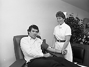 Tony Ward Gives Blood..1984.16.03.1984.03.16.1984.16th March 1984..With a possible shortage of blood over the St Patrick's Weekend,Tony Ward,Irish Rugby International,led an awareness campaign by donating blood. He attended The Blood Transfusion Service,Pelican House,Mespil Road,Dublin...Photograph of Tony all hooked up and ready to donate. Here he is in the capable hands of Nurse Barbara Maguire, Donor Team Leader/Attendant.