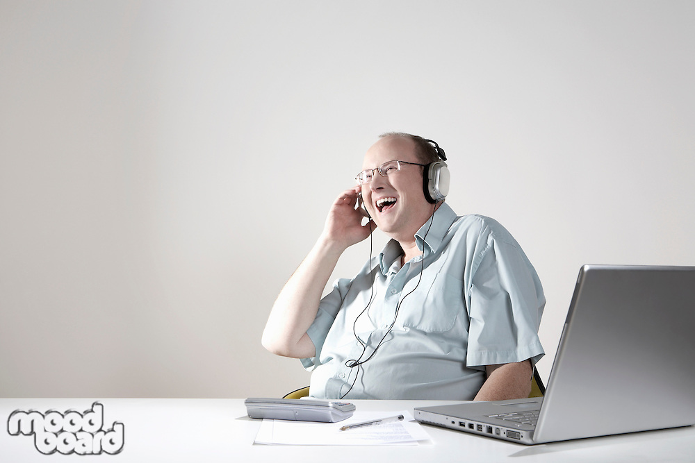 Businessman with earphones laughing at desk