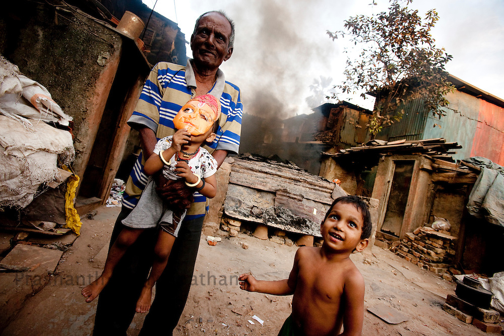 "Children play next to pottery klins in the Daharavi slum area in Mumbai, India, on Jan. 30, 2009. A sprawling slum area in the heart of the fastest growing city in the world, Dharavi and its affiliate slum areas have been thrust into limelight in the year 2008 like never before. Earlier it was the slum redevelopment authorities who threatened to break down the shanties and build new infrastructural projects, and during the far end of the year it was the movie ""Slum Dog Millionaire"". Winning Gloden Globes, 8 Oscar's & 7 Bafta's the movie has bought to light the ruggedness and the struggle of the life in the slums of Indian cities. While the movie is a fairy tale story of positive endings the real hardship, unemployment and economic disparities seen in the slums is striking and deplorable. Yet the slums of Mumbai offer hope and oppurtunity to the few who travel and live away from their native villages and try make a living out of India's growth curve and rapid industrial progress. .. 2009 brings with it, recession, downturn and unemployment. In this scenario the life in the slum gets more rugged and difficult. This photo essay is a peek into the daily lives of city slum dwellers who live, hope, dream, relax, enjoy in the premises of these slums at the fringes of progress and development awaiting for an oppurtunity to break free into the other side."