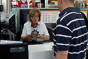 Mature lady employee at British Airways check-in at Heathrow Airport's Terminal 5.