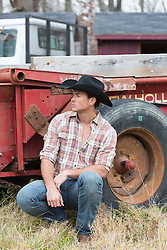 cowboy leaning against a truck on a ranch