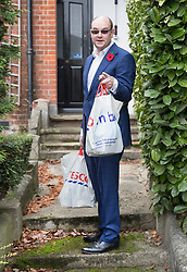 © Licensed to London News Pictures. 09/11/2017. Whitam, UK. Alex Sawyer, husband of Priti Patel, talks to reporters as he arrives home with two bags of shopping. Priti Patel resigned from government yesterday. Photo credit: Peter Macdiarmid/LNP