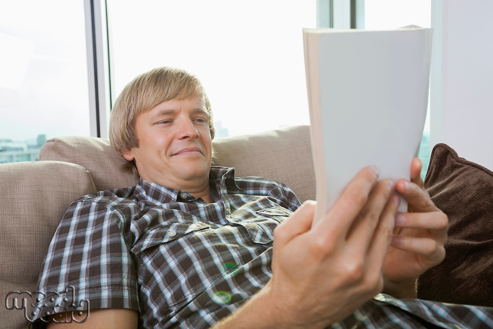 Relaxed mid-adult man reading book in living room at home