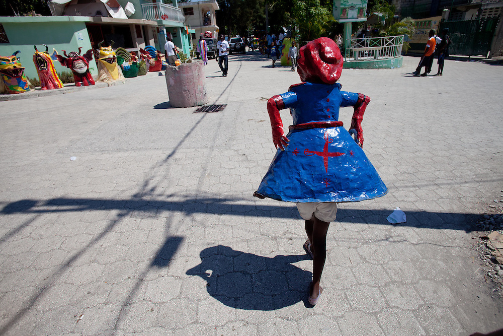 The carnival celebrations in Jacmel are famous for intricate paper mache masks and street theater. Carnival celebrations did not happen last year in Haiti becuase of the January 12th earthquake. For many of the artisans in Jacmel the revenue from carnival is their primary source of income./// A young girl carries a paper mache carnival mask on the road.