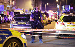 """An armed police officer mans a cordon on the Seven Sisters Road at Finsbury Park in north London, where one person has been arrested after a vehicle struck pedestrians, leaving """"a number of casualties""""."""