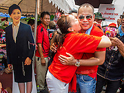 06 APRIL 2014 - BANGKOK, THAILAND: NATTAWUT SAIKUA, a Red Shirt core leader, is hugged by a Red Shirt as he walks through the crowd at a Red Shirt rally in a Bangkok suburb Sunday. The woman hugged him as he passed a cardboard cutout of Prime Minister Yingluck Shinawatra (left). Red Shirts and supporters of the government of Yingluck Shinawatra, the Prime Minister of Thailand, gathered in a suburb of Bangkok this weekend to show support for the government. The Thai government is dealing with ongoing protests led by anti-government activists. Legal challenges filed by critics of the government could bring the government down as soon as the end of April. The Red Shirt rally this weekend was to show support for the government, which public opinion polls show still has the support of most of the electorate.   PHOTO BY JACK KURTZ