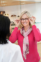 Portrait of a senior woman trying on glasses in store